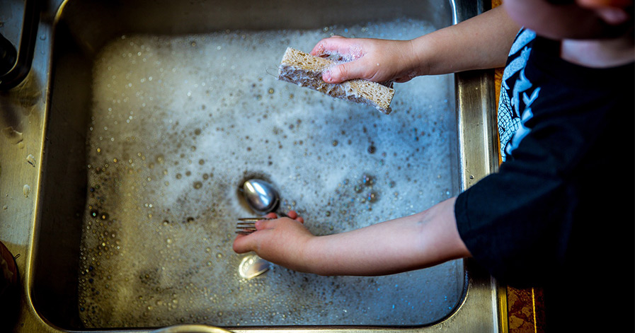 Child washing dishes in sink filled with suds