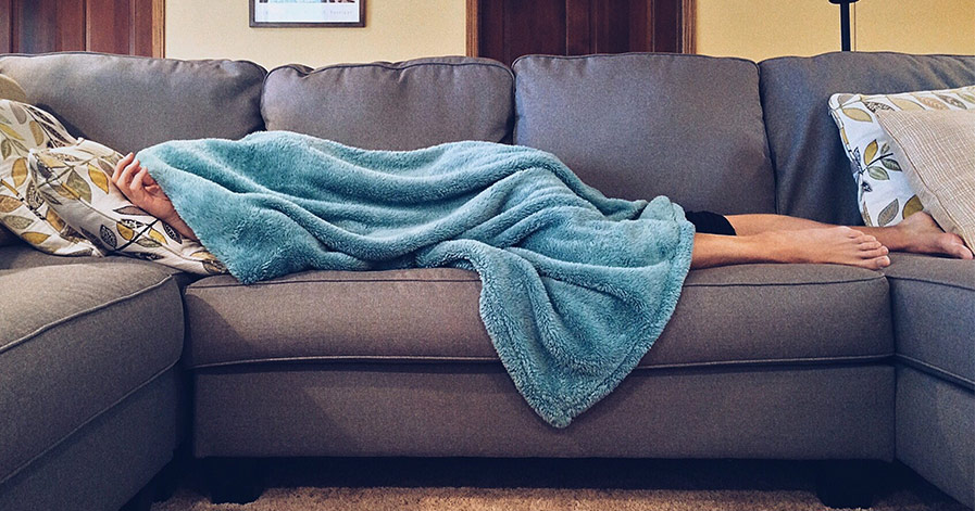 Person sick on couch under blanket
