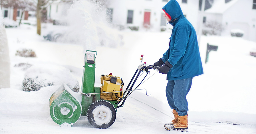 Person pushing snow blower in winter