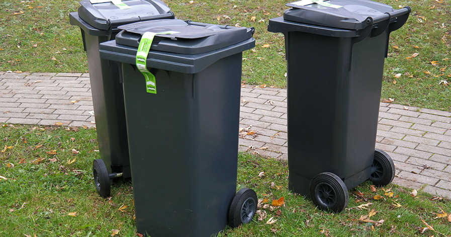 Three outdoor trash cans