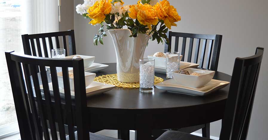 Dining room table with flowers in vase sitting on top