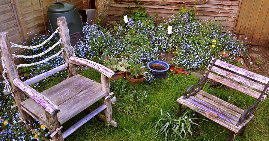Patio furniture in backyard beside flower garden