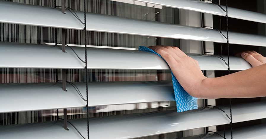A person cleaning blinds in their home