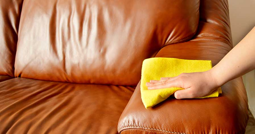 A person wiping down a leather sofa.