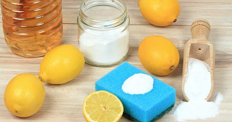 Green cleaning supplies, including lemons, baking soda, and vinegar.