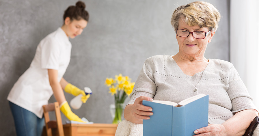 a senior citizen reading a book while a cleaning service works