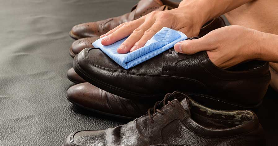 Someone cleaning a pair of leather shoes