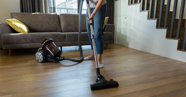 Woman vacuuming hardwood floor in living room area
