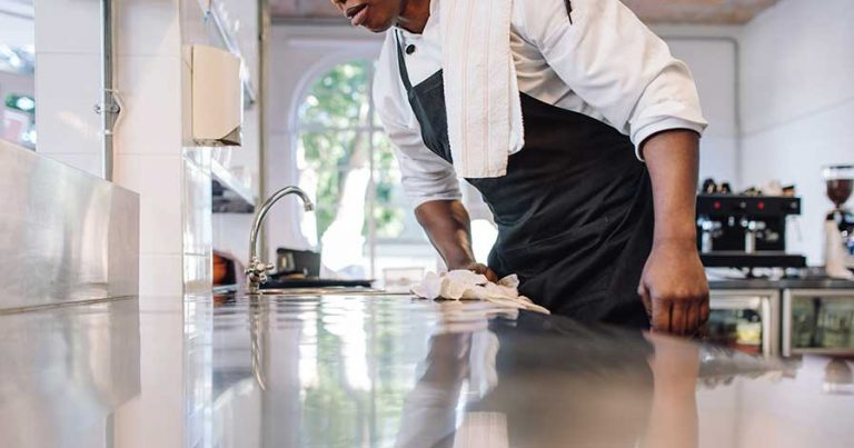 A staff member cleaning counters in a restaurant