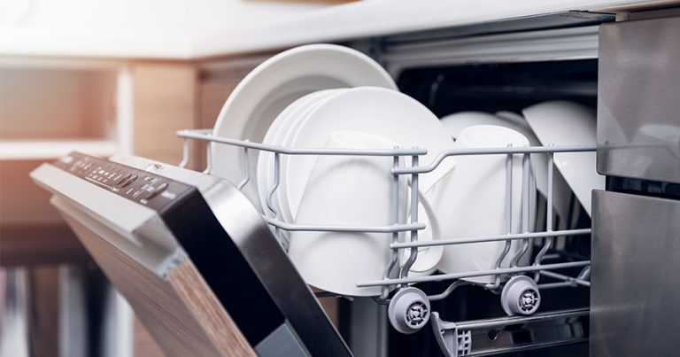 Dishwasher partly open with top tray full of dishes