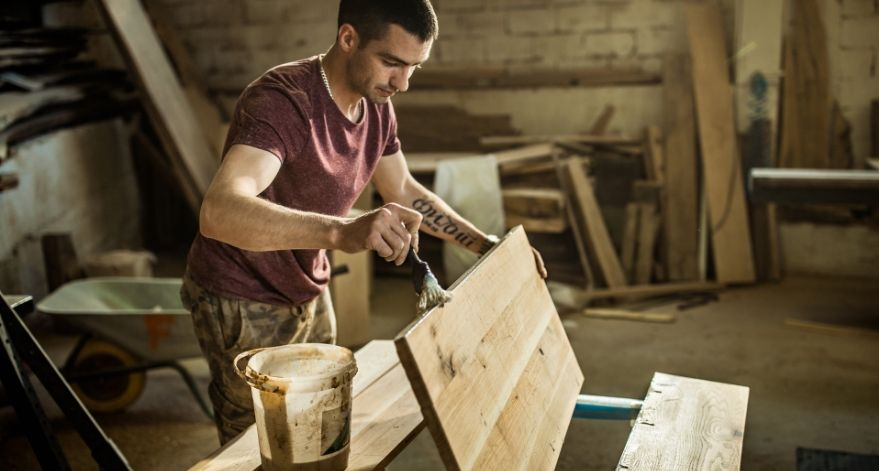 A man staining wood in his shed.