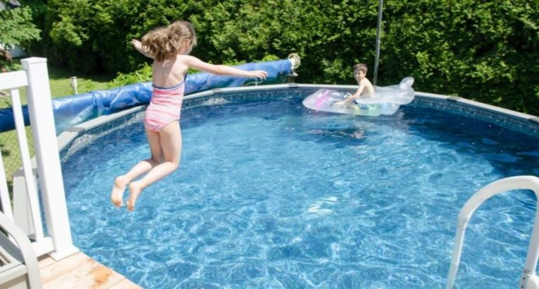 Kids are enjoying their summer by swimming in their above ground pool.