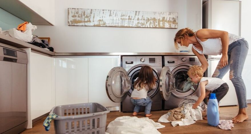 A mom and her kid are doing laundry.
