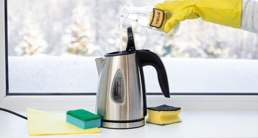Someone pouring vinegar into their electric kettle to clean it.