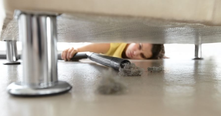 A lady vacuuming underneath her couch.