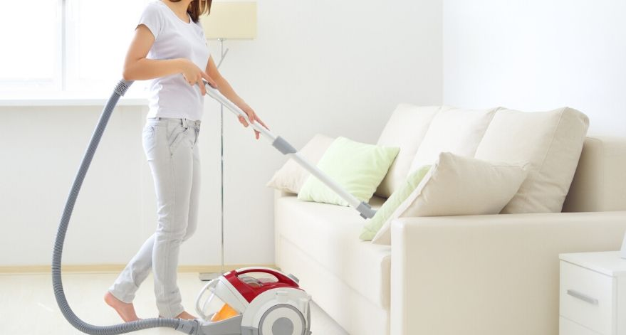 A woman is vacuuming her couch.