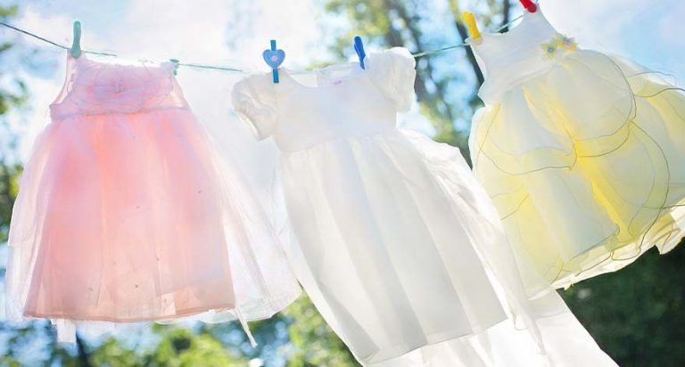 A pink dress, a white dress and a yellow dress hanging on a clothesline on a sunny day.