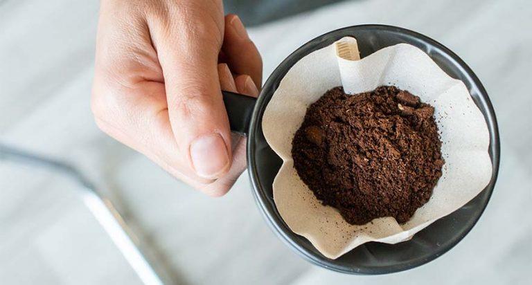 A mug with coffee grounds inside a coffee filter.