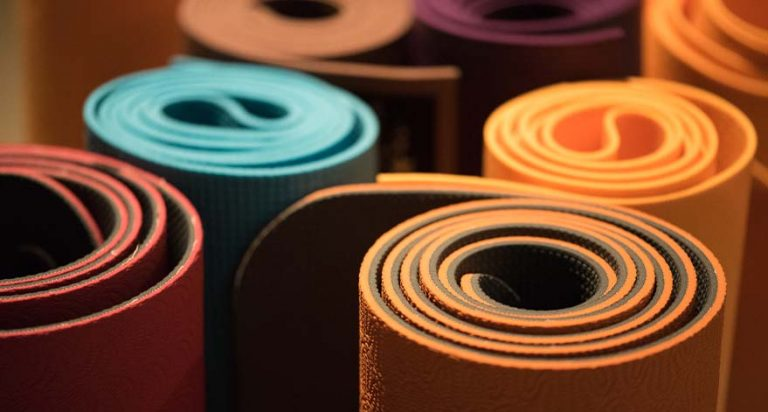 Rows of red, blue and yellow yoga mats.