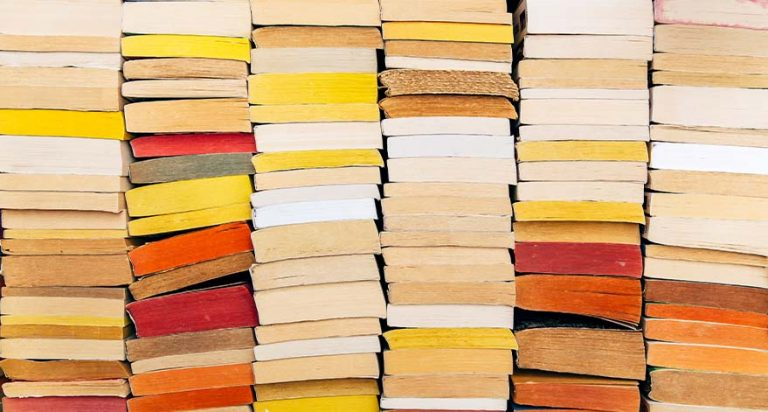 Stacks of yellow, red and brown books.