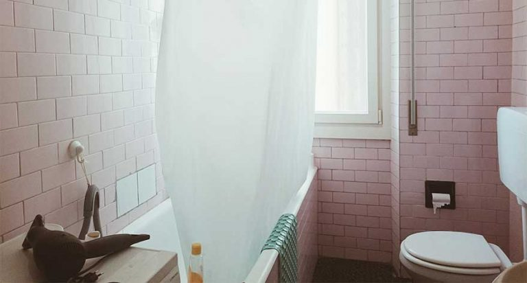 A white shower curtain hanging in a bathroom.